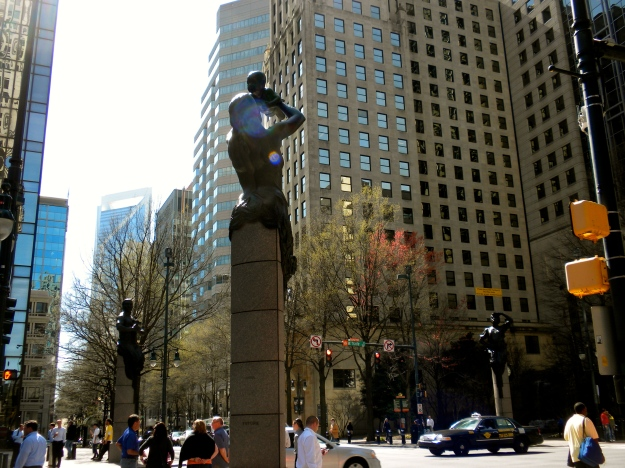 Bronze statues stand at the each corner at the intersection of Trade & Tryon.  Duke Energy building in the background (the one with the whole in the top)