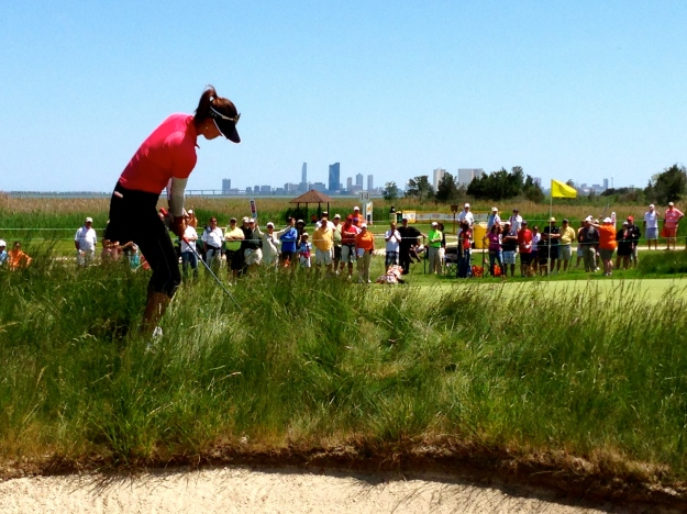 Michelle Wie hitting out of the junk.  Atlantic City skyline behind her